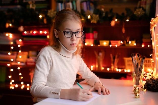 Urocza mała dziewczynka pisze list do santa klaus siedzącego na stole
