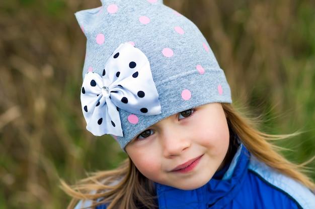 Urocza mała dziewczynka pozuje na zamazanym tle i ono uśmiecha się wewnątrz kamera. na sobie płaszcz zimowy i czapkę. urocza młoda dziewczyna w jesieni outdoors.