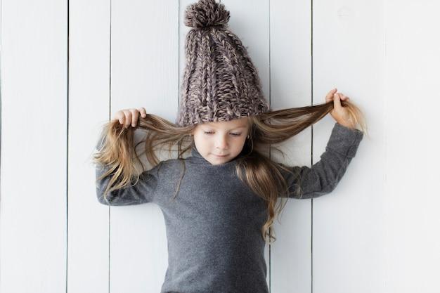 Urocza mała dziewczynka pozuje obok biel ściany