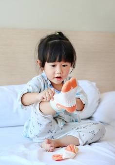 Urocza mała dziewczynka próbuje stawiać skarpety na łóżku.