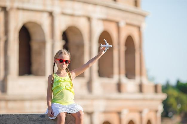 Urocza mała dziewczynka przed colosseum w rzym, włochy. dziecko w włoskich wakacjach