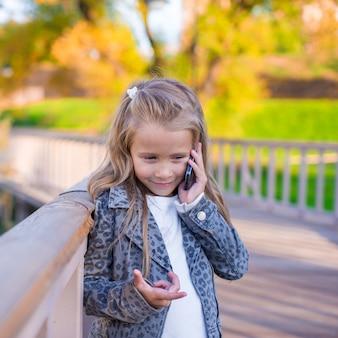 Urocza mała dziewczynka przy ciepłym jesień dniem outdoors