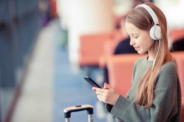 Urocza mała dziewczynka przy lotniskiem w dużym lotnisku międzynarodowym blisko okno