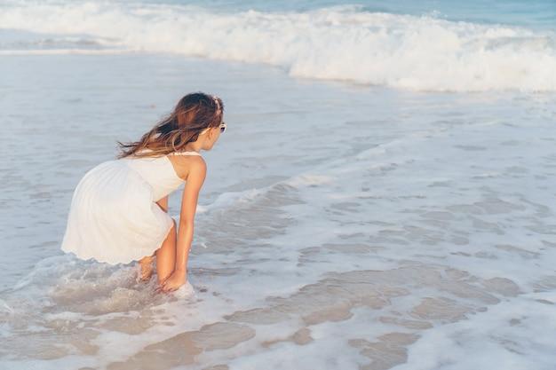 Urocza mała dziewczynka przy plażą ma mnóstwo zabawę w płytkiej wodzie