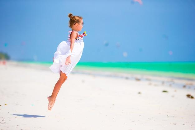 Urocza mała dziewczynka przy plażą podczas wakacje. słodkie dziecko, zabawy, skoki i cieszyć się jej wakacje na plaży