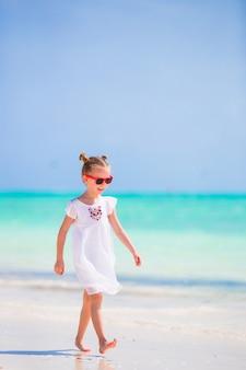 Urocza mała dziewczynka przy plażą podczas wakacje