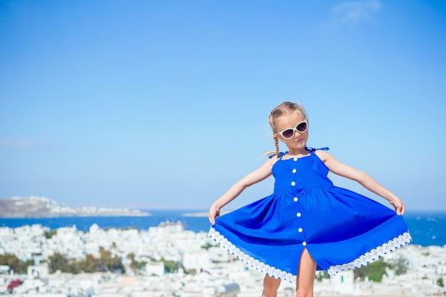 Urocza mała dziewczynka przy starą ulicą typowa grecka tradycyjna wioska