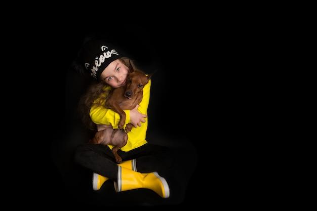 Urocza mała dziewczynka przytula swojego psa, pinczera miniaturowego. strzelanie studyjne na czarnym tle. pojęcie miłości do natury, ochrony zwierząt, niewinności, zabawy. zdjęcie wysokiej jakości