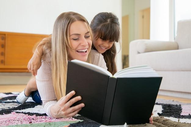 Urocza mała dziewczynka przytulanie mamy, uśmiechając się i słuchając historii.
