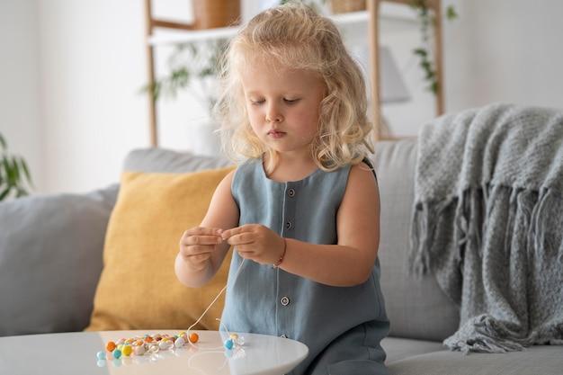 Urocza mała dziewczynka robi akcesoria z różnymi kolorowymi kulkami