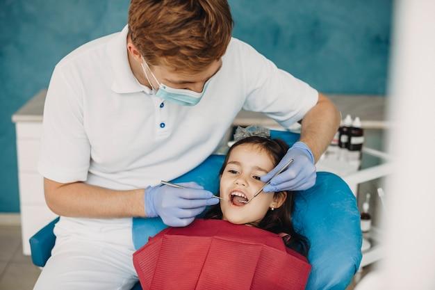 Urocza mała dziewczynka robi badanie zębów w stomatologii dziecięcej.