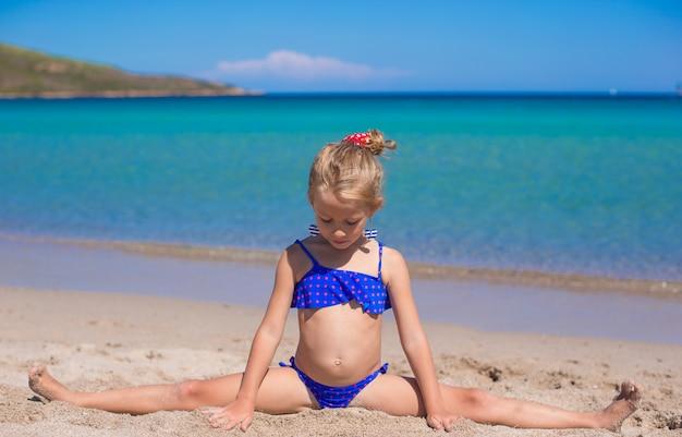 Urocza mała dziewczynka robi kołu na tropikalnej białej piaskowatej plaży