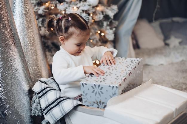 Urocza mała dziewczynka rozpakowuje prezent na boże narodzenie.