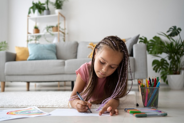 Urocza mała dziewczynka rysująca na papierze w domu