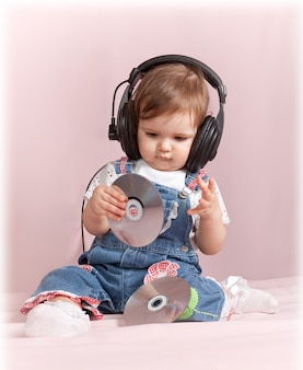 Urocza mała dziewczynka siedzi i słucha muzyki na różowo