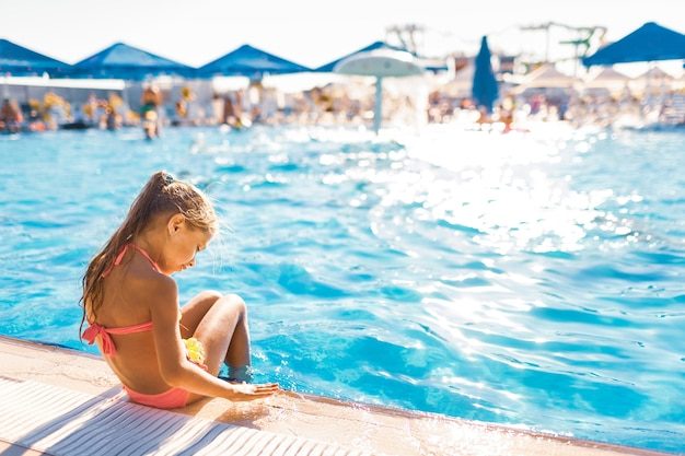Urocza mała dziewczynka siedzi na brzegu basenu z nogami w wodzie, ciesząc się słońcem?