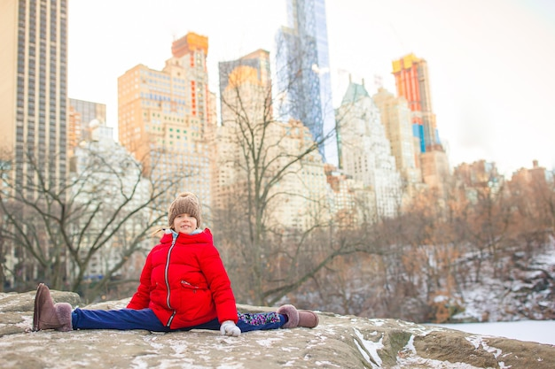 Urocza mała dziewczynka siedzi na lodowisku w central parku w nowym jorku