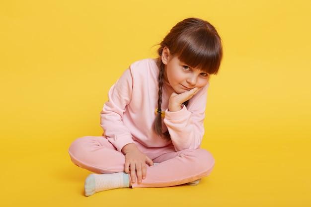 Urocza mała dziewczynka siedzi na podłodze ze skrzyżowanymi nogami, trzymając dłoń na brodzie, patrzy znudzona w kamerę, dziecko płci żeńskiej w różowym, swobodnym stroju, dziecko chce się bawić, nie wie, co robić.