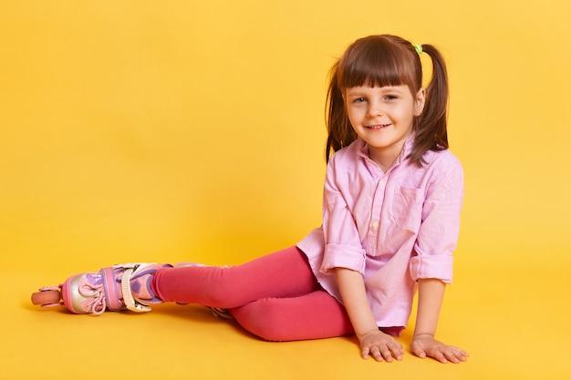 Urocza mała dziewczynka siedzi na podłodze.