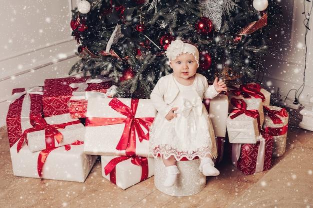 Urocza mała dziewczynka siedzi na pudełku blisko choinki dekorującej z ornamentami. białe pudełka z czerwonymi kokardkami pod drzewem. ładne dziecko ubrane w białą sukienkę. efekt śniegu.