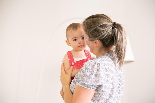 Urocza mała dziewczynka siedzi na rękach mamy. blondynka matka trzyma córkę, rozmawia z nią i uśmiecha się. pojęcie czasu dla rodziny, macierzyństwa i bycia w domu