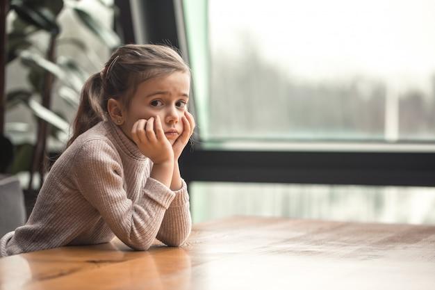 Urocza mała dziewczynka siedzi przy drewnianym stole przy oknie.
