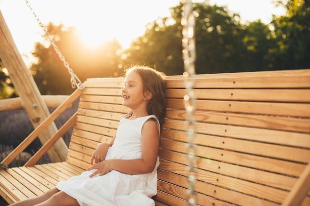 Urocza mała dziewczynka śmiejąc się podczas zabawy na drewnianej huśtawce na zewnątrz przed zachodem słońca.
