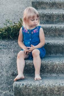Urocza mała dziewczynka śmiejąca się z natury - szczęśliwa dziewczyna w niebieskiej sukience i bita po kolana siedzi na schodach. szczęśliwe dzieciństwo.
