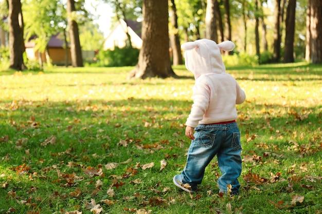 Urocza mała dziewczynka spaceru w jesiennym parku