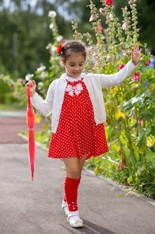 Urocza mała dziewczynka spaceruje w czerwonej sukience i białej bluzce z różowym składanym parasolem w letni dzień