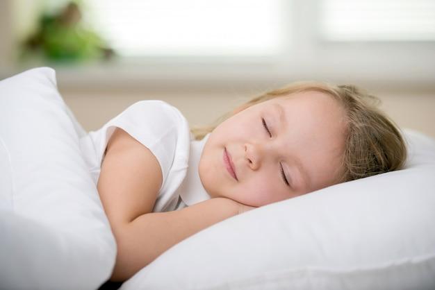 Urocza mała dziewczynka śpi na białym łóżku.