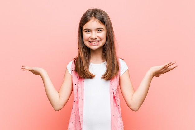Urocza mała dziewczynka sprawia, że waga z rękami, czuje się szczęśliwa i pewna siebie.