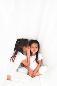 Urocza mała dziewczynka szepcze coś do swojej siostry pod przykryciem