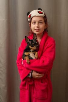 Urocza mała dziewczynka trzyma chihuahua szczeniaka stojąc i patrząc w górę. dziewczyna trzyma psy chihuahua w ramionach. dziewczynka 9 lat ze zwierzakiem w domu w ramionach. pojęcie miłości do zwierząt. dom