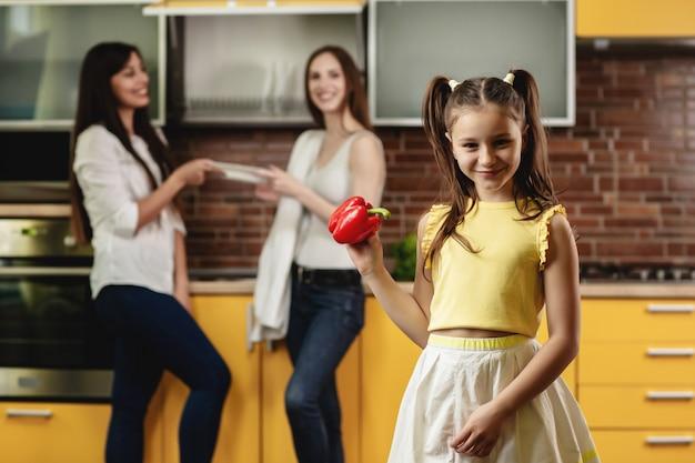 Urocza mała dziewczynka trzyma słodkiego pieprzu i patrzeje je. szczęśliwa dziewczyna stoi w kuchni, patrząc na kamery, bawi się dużą papryką. w tle dwie kobiety układają naczynia