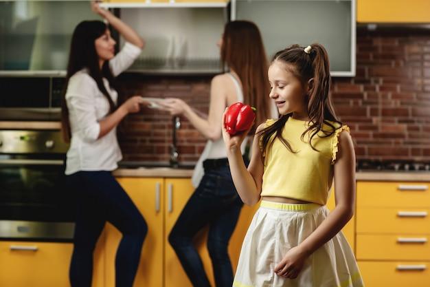 Urocza mała dziewczynka trzyma słodkiego pieprzu i patrzeje je. szczęśliwa dziewczyny pozycja w kuchni i bawić się z dużą papryką. w tle dwie kobiety układają naczynia. reklama zdrowego odżywiania