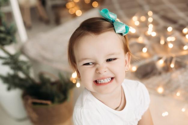 Urocza mała dziewczynka ubrana w białą koszulkę i posiadająca turkusową kokardkę na głowie