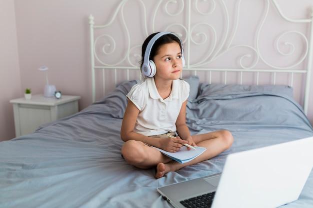 Urocza mała dziewczynka używa jej laptop