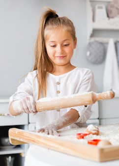 Urocza mała dziewczynka używa kuchennego rolownika