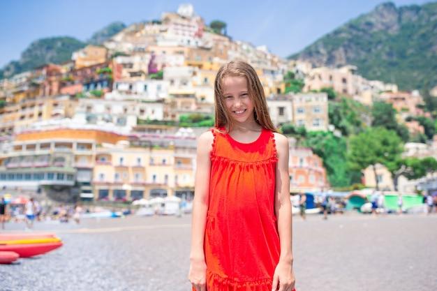 Urocza mała dziewczynka w ciepły i słoneczny letni dzień w miasteczku positano we włoszech
