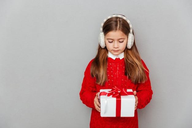 Urocza mała dziewczynka w czerwonym swetrze i nausznikach trzymająca pudełko na prezent