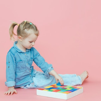 Urocza mała dziewczynka w drelichowych ubraniach na różowym tle