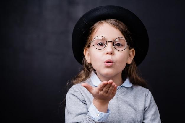 Urocza mała dziewczynka w eleganckiej odzieży codziennej i okularach, dając ci pocałunek powietrza w izolacji