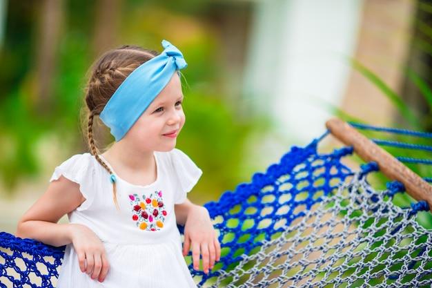 Urocza mała dziewczynka w hamaku plenerowym przy plażą