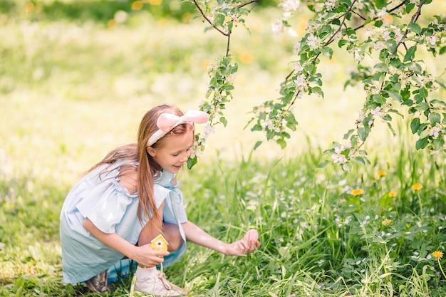 Urocza mała dziewczynka w kwitnącym jabłko ogródzie na pięknym wiosna dniu