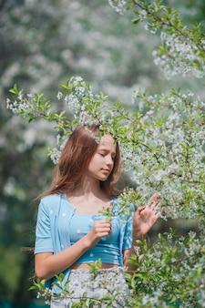 Urocza mała dziewczynka w kwitnącym ogrodzie jabłkowym w piękny wiosenny dzień