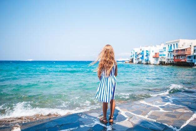 Urocza mała dziewczynka w little venice, najpopularniejszym regionie turystycznym na wyspie mykonos w grecji.