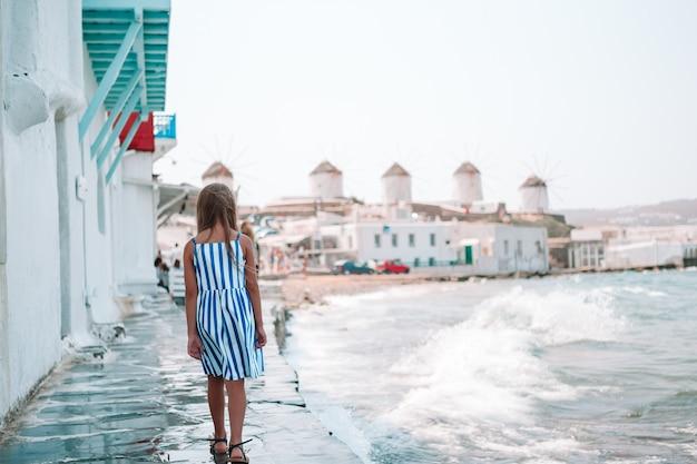 Urocza mała dziewczynka w małej wenecji najbardziej popularnym regionie turystycznym na wyspie mykonos, grecja.