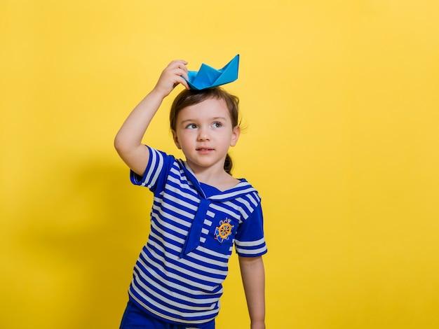 Urocza mała dziewczynka w marynarskim garniturze trzyma papierową łódkę na głowie i spogląda na żółtą przestrzeń. dzień marynarki wojennej.