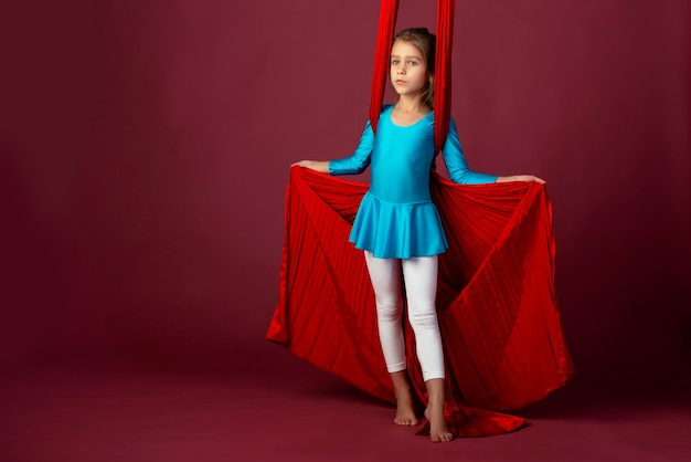Urocza mała dziewczynka w niebieskim stroju gimnastycznym przygotowana do występu